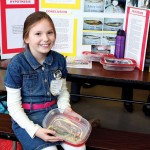"Giulianna Pinevich, 8, shows off her mummified fish. She found that a mixture of salt, baking soda and borax mummify fish the best. Pinevich said her parents are glad the experiment is over. ""My whole kitchen was smelly,"" she said."
