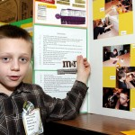 "Robert Hanson, 8, explains the results of his edible chocolate melting experiment. He predicted that M&Ms would melt the slowest because of their hard candy coating. His hypothesis proved correct, but he also found that chocolate with higher coco content took longer to melt. ""I love chocolate,"" Hansen said when asked why he chose that experiment."