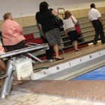 Members of the Board of Education, Board of Finance, and Board of Mayor and Burgesses walk through the pool at Naugatuck High School during a tour Aug. 25. Renovation plans for the building would move the bleachers to an upper balcony and bring the pool up to code.